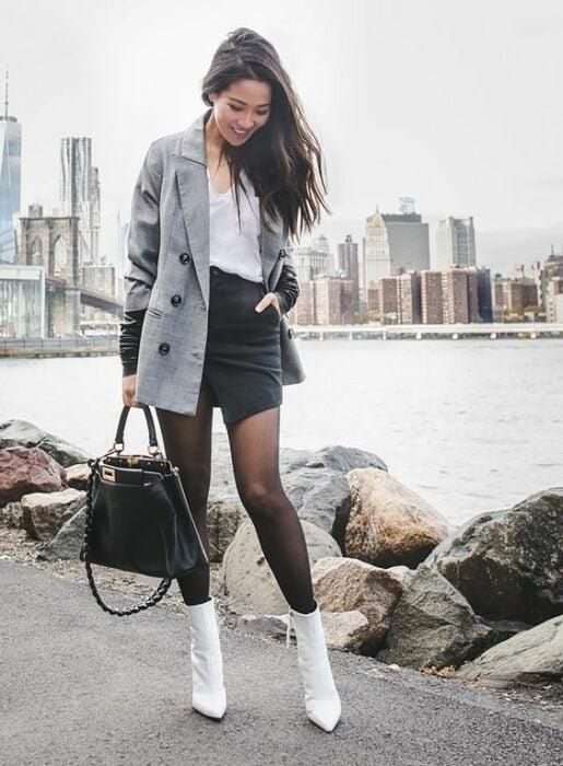 Chica usando botines blancos y medias negras, mini falda de vinil, y blusa blanca además de blazer gris con bolso de mano negro
