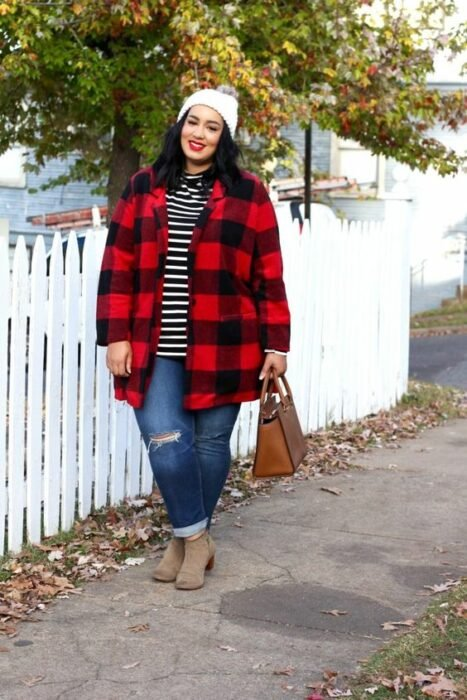Curvy girl wearing ripped jeans, camel ankle boots, black blouse with white lines and red jacket with black squares