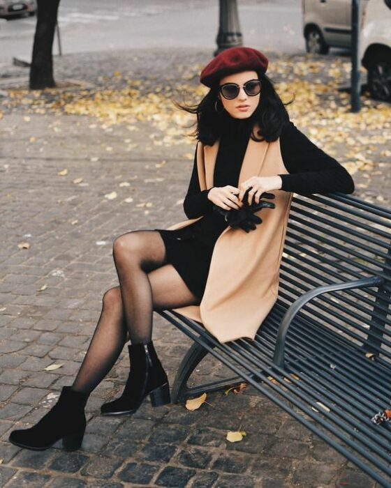 Outfit for the autumn-winter office with cherry beret, black long-sleeved dress, long caki vest, black stockings and ankle boots