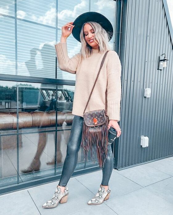 Girl wearing python boots with denim jeans, beige sweater, black hat and brown tote bag