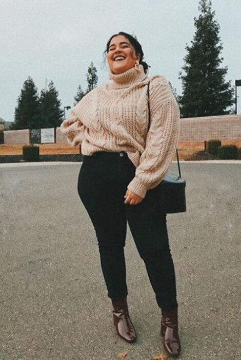 Curvy girl wearing black jeans, brown ankle boots, and coral pink turtleneck sweater