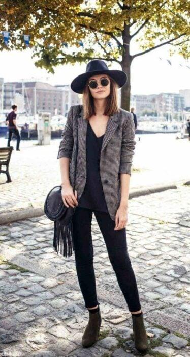 Chica usando sombrero de color negro con outfit de botines, jeans y blusa negra y blazer gris