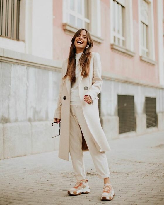Girl wearing a total white tennis look, dress pants, blouse and long coat
