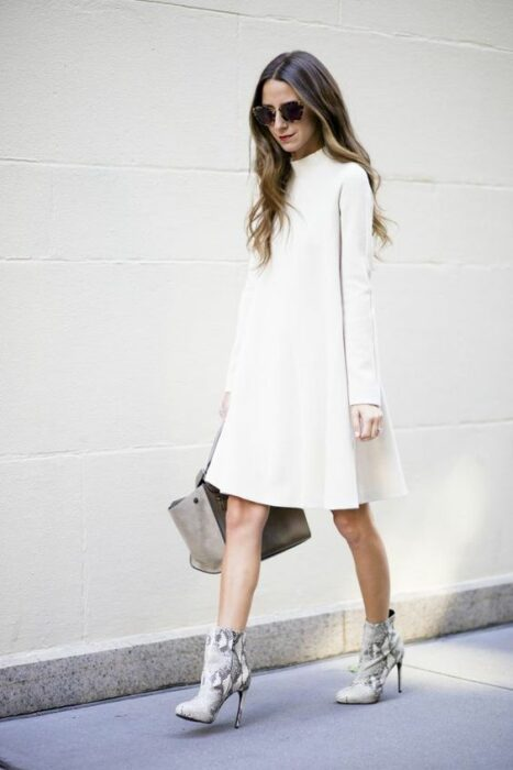 Girl wearing python boots with long-sleeved white dress and sand-colored handbag, and sunglasses