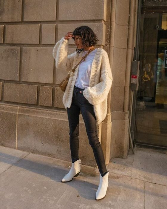 Chica usando botines blancos y jeans deslavados negros, blusa blanca y suéter holgado beige
