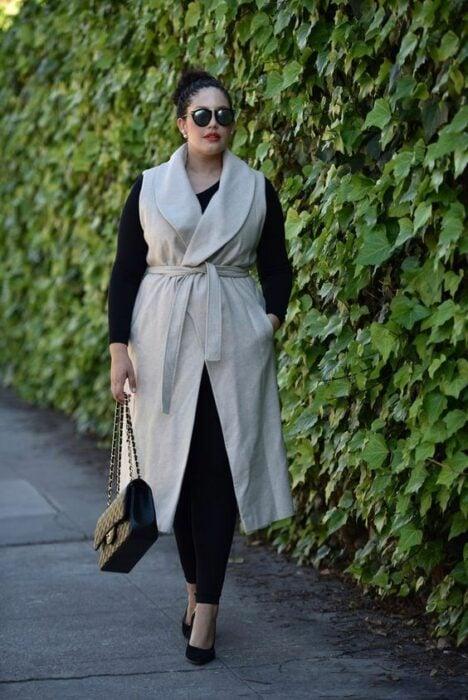 Curvy girl wearing heels, leggings and black sweater and long beige vest with black handbag