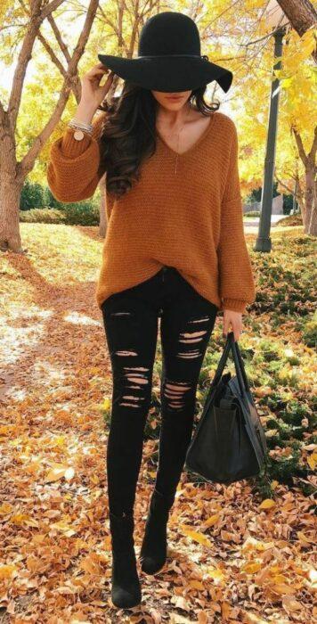 Chica usando sombrero de color negro con outfit de botines y jeans rasgados negros, cion un suéter camel holgado