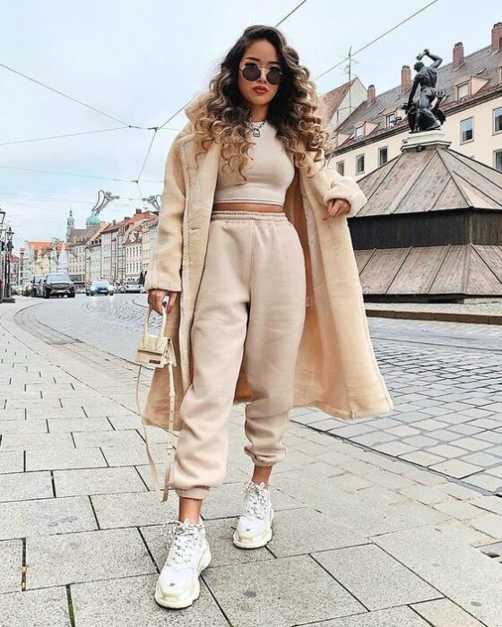 Girl wearing a total white tennis look, sweatpants, crop top and furry coat