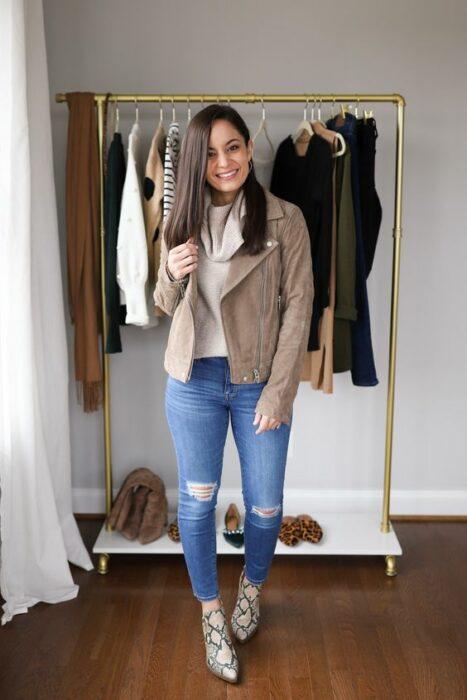 Chica usando botas pitón con jeans rasgadps, blusa blanca y sacocolor caki