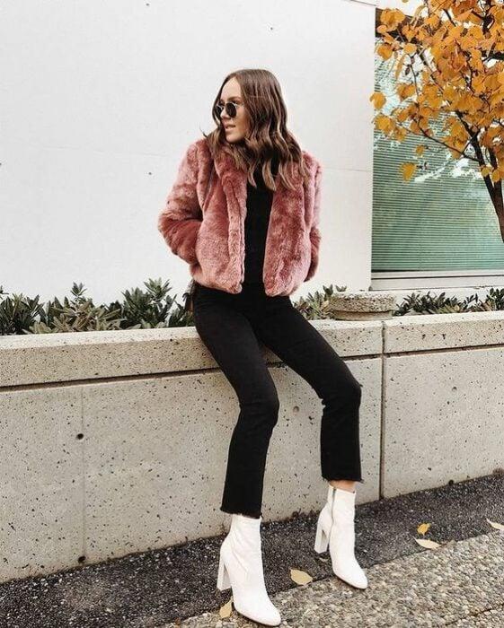 Chica usando botines blancos y jeans negros, blusa negra y saco furry de color rosa palo