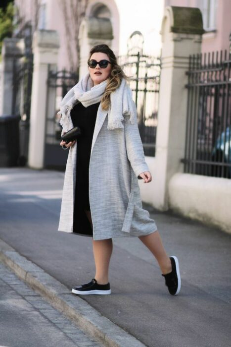 Curvy girl wearing black tennis shoes, black dress, beige coat and scarf of the same color
