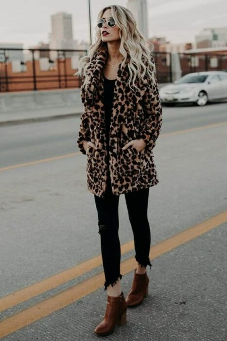 Autumn-winter office outfit with furry animal print coat, black blouse and jeans and camel ankle boots