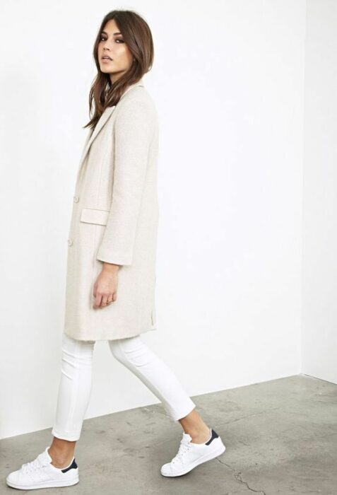 Girl wearing a total white look of tenus, jeans and long blazer