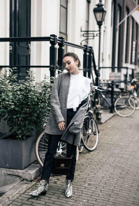 Chica usando botas pitón con pantalón de vestir negro, blusa blanca y blazer gris, con bolsa de mano color negra
