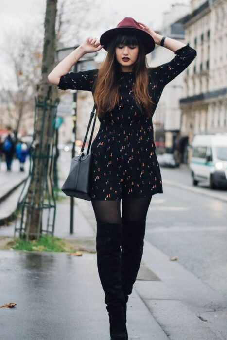 Girl wearing cherry hat with outfit of black stockings and ankle boots and black dress with white polka dots