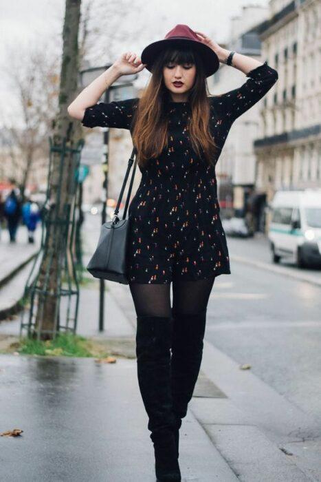 Chica usando sombrero de color guinda con outfit de medias y botines negros y vestido negro con lunares blancos