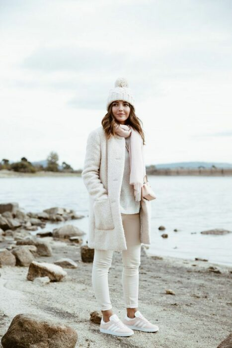Girl wearing a total white tennis look, pants, sweater, long coat, scarf and hat