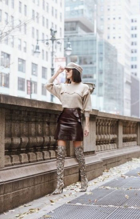 Girl wearing python boots with brown mini skirt, beige blouse, sunglasses and beige beret