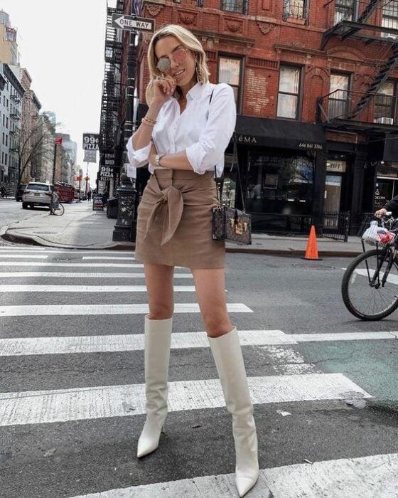 Chica usando botas blancas y mini falda color caki, con camisa color blanca de manga tres cuartos