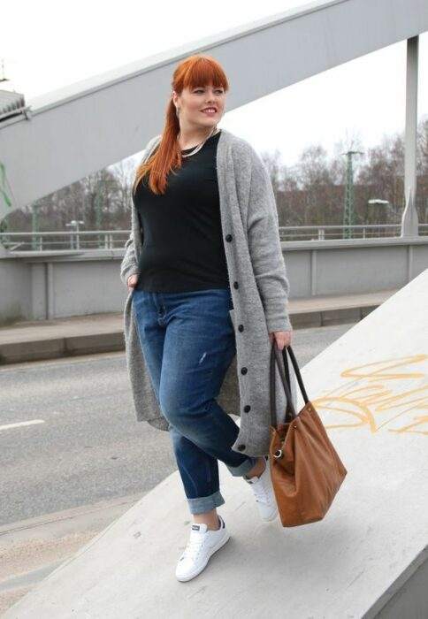 Curvy girl wearing jeans, white tennis shoes, black sweater and long gray cardigan, with camel bag