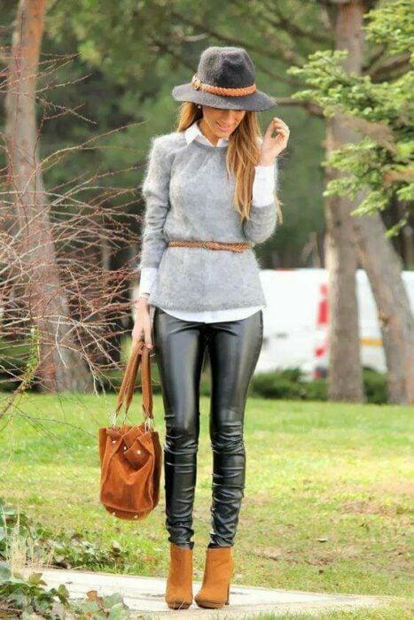 Chica usando sombrero de color gris con outfit de botines color camel, leggings de vinil, camisa blanca con un suéter gris y cinturón camel