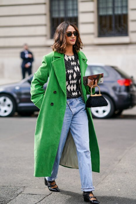 Girl wearing a long green coat with a diamond sweater and jeans