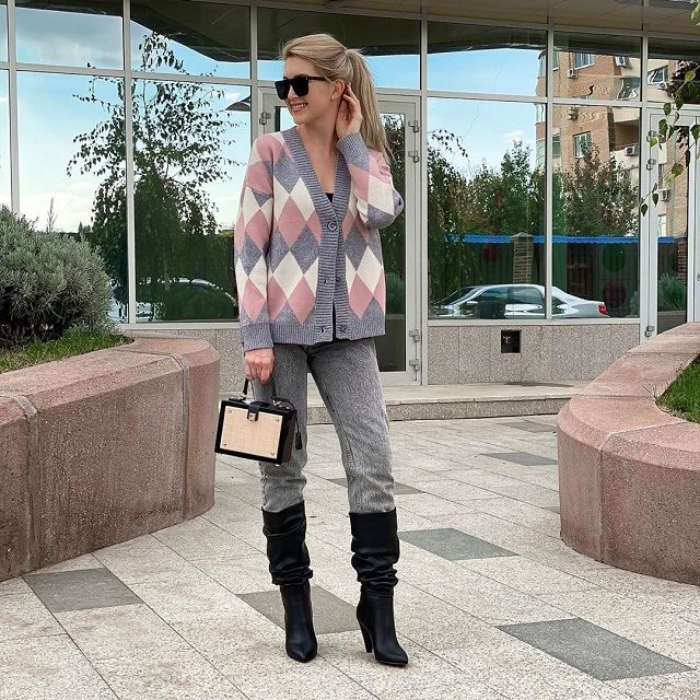 Girl wearing oversized multi colored diamond pattern sweater with black jeans and boots