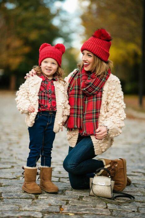 Madre e hija pequeña ambas vistiendo gorrito rojo, camisa tartán roja con verde, suéter blanco con bolitas, jeans oscuros y botas estilo ugg color café