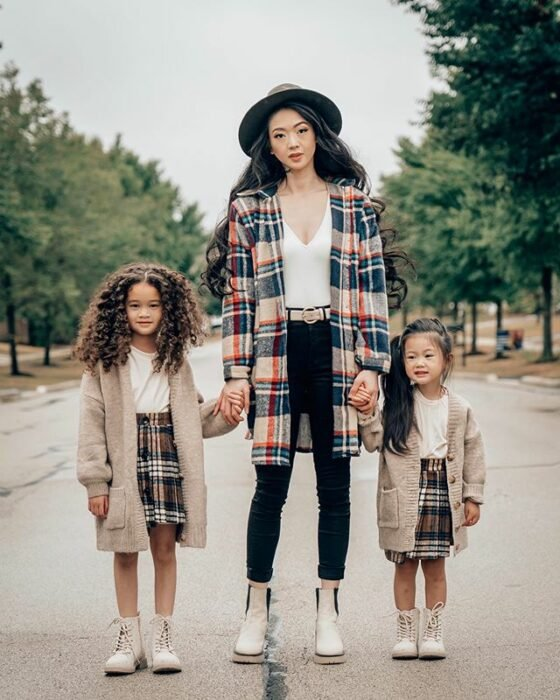 Asian and slim mother with long wavy hair with a gray hat wearing a white blouse, black pants, white ankle boots and a beige, red and blue plaid jacket, holds the hands of her two daughters who are wearing beige ankle boots, a brown and white plaid skirt , white blouse and long cardigan in beige tones