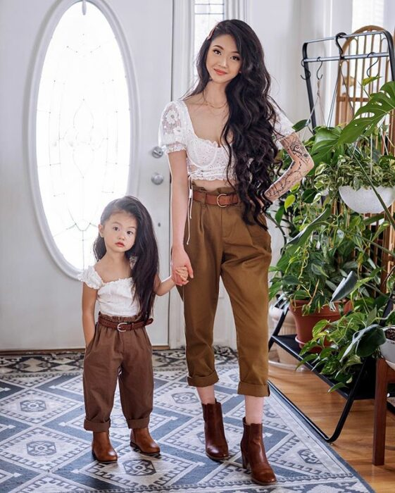 Mother and daughter posing at the entrance of their house with white walls and green plants to decorate one side, both wearing brown pants, brown ankle boots, white lace blouse and long wavy hair combed to the side