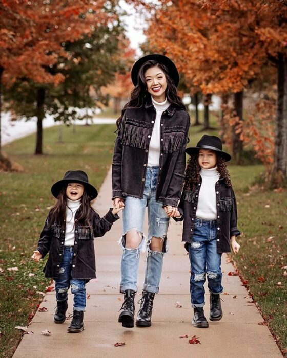 Mother and her two daughters holding hands in a park with orange-leafed trees, the three of them wearing light jeans, black ankle boots, a white blouse, a long black jacket with small 'beards' on the bust, and wide black hats