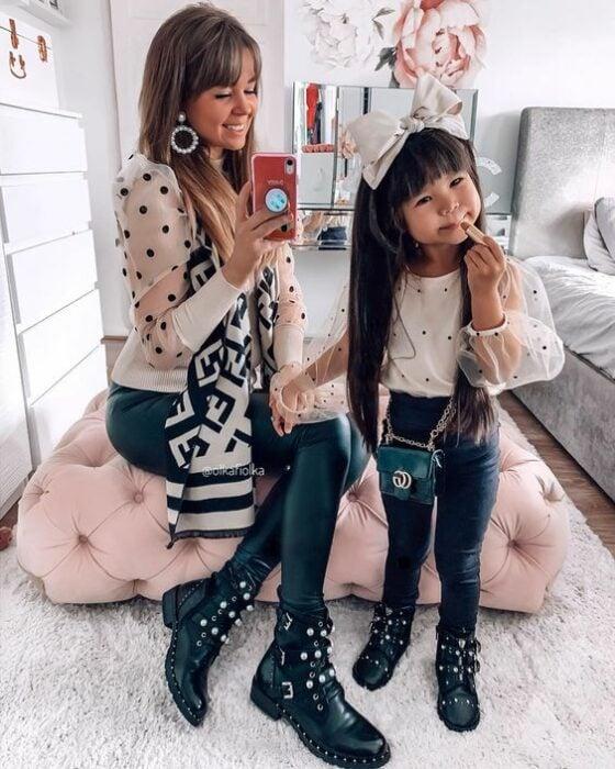 Madre de cabello rubio sentada en un cojín grande rosa y su hija de cabello largo, negro y lacio se toman selfie frente al espejo ambas vistiendo mallones negros, botines negros con aplicaciones blancas y plateadas y una blusa blanca con puntos negros con transparencias en las mangas