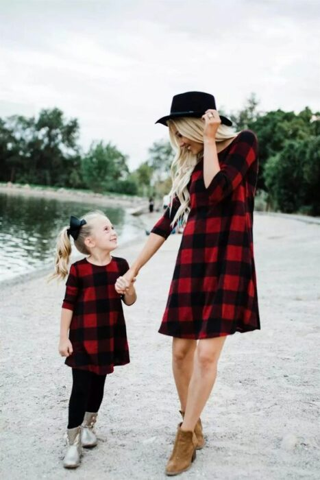 Mother and daughter holding hands near a lake both in red dress like black plaid, the mother wears brown ankle boots and black hat with long, blonde and wavy hair and the girl wears black leggings with silver boots with high side ponytail and a big black bow
