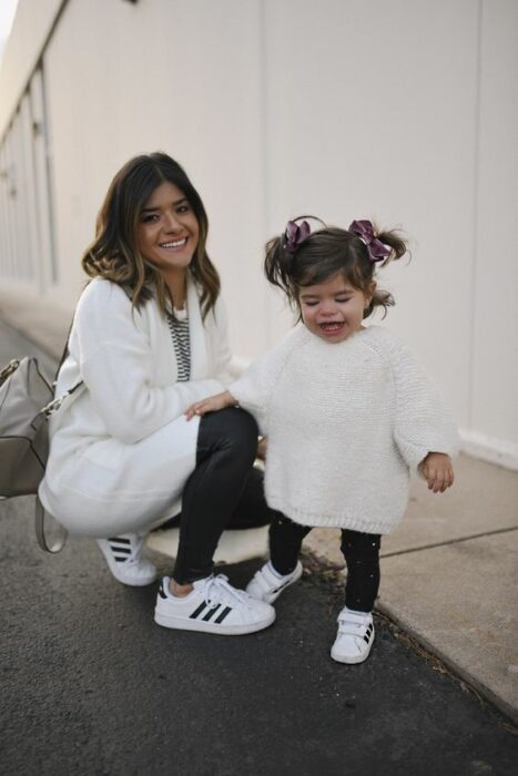 Leaning mother wearing dark jeans, black striped white tennis shoes, black and white striped blouse and a white cardigan holds her little daughter combed with two high ponytails tied with purple velvet bows while wearing long white sweater, black leggings and white tape