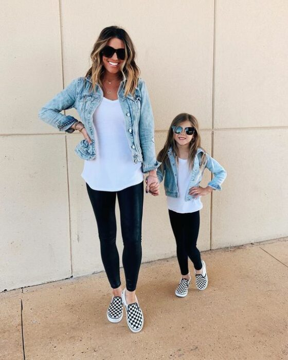 Blonde haired mother and daughter holding hands while wearing black leggings, white vans with black plaid, long white blouse, denim jacket and dark sunglasses and have their hands on their waist