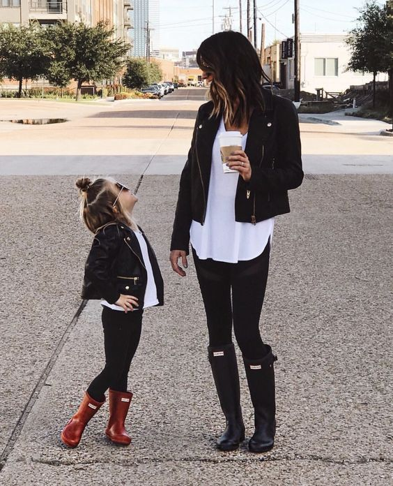 Mother and little daughter posing in the street while wearing black jeans, white blouses, black leather jackets and the girl wears red rain boots and has dark sunglasses and the mother wears black rain boots while holding a starbucks coffee