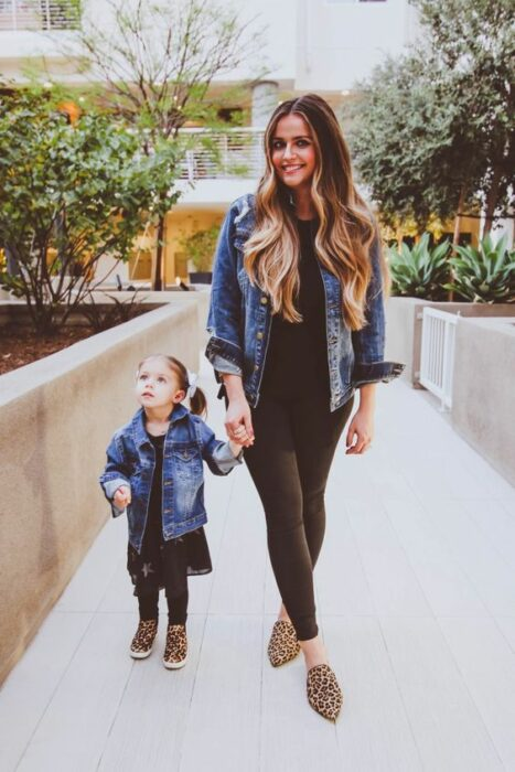 Mother and little daughter holding hands walking down the street wearing matching outfits with black dress and pants, dark denim jacket and shoes in 'animal print'