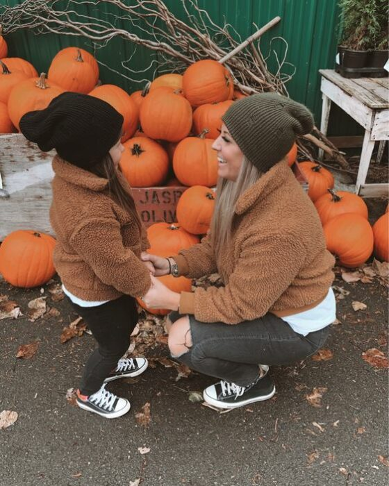 Mother and little daughter in pumpkin patch holding hands with matching outfits with black pants, black converse, white blouse, brown teddy-style coat and black and green hat