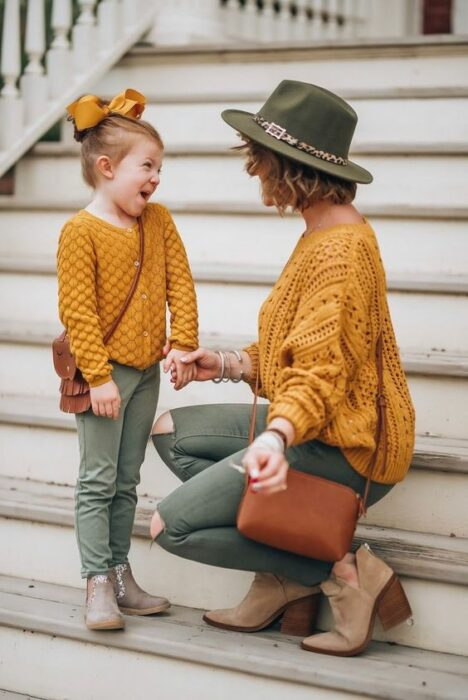 Mother and daughter smiling on white steps, both in the same outfit of olive green pants, beige ankle boots, mustard yellow knitted sweater, camel bag, while the girl wears a large yellow bow and the mother an olive green hat