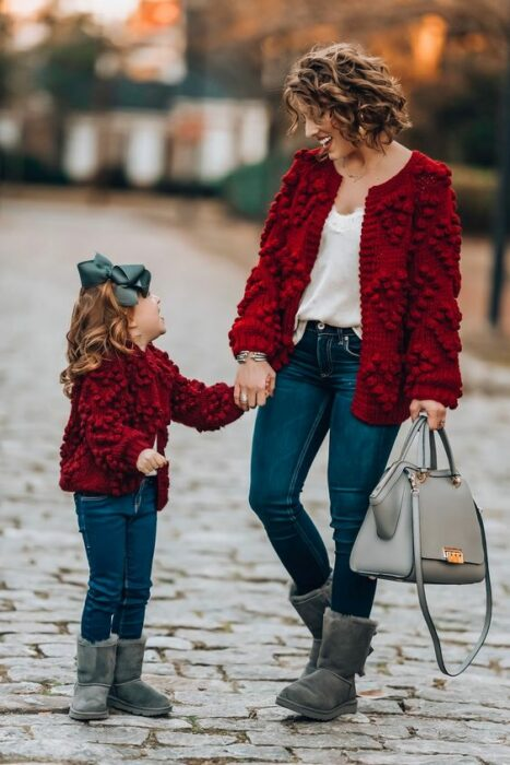 Mother and daughter holding hands walking in the street, both wearing gray UGG boots, navy blue jeans, white blouse and red coat with little balls. The girl wears a large olive green bow in her hair and the mother carries a gray purse in her left hand