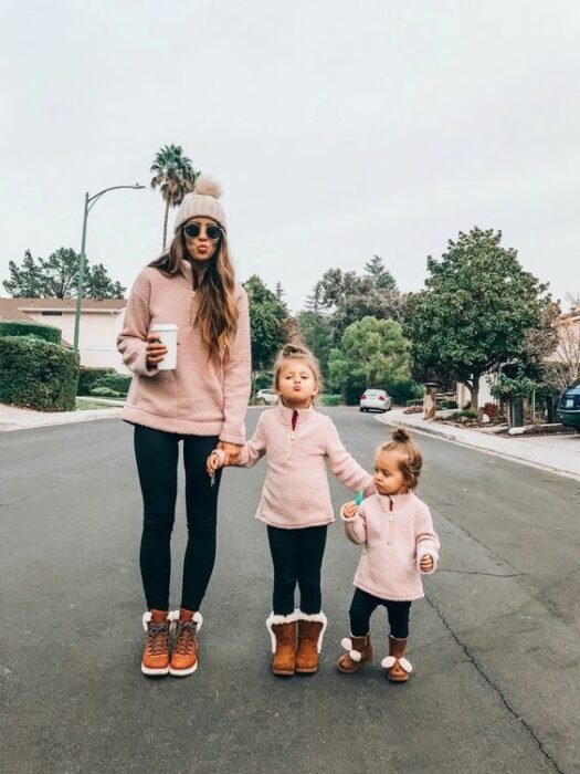 Mother and her two daughters wear black leggings, brown boots with white and pastel pink sweatshirt. The mother holds a white cup of coffee, while wearing black sunglasses and a pink hat