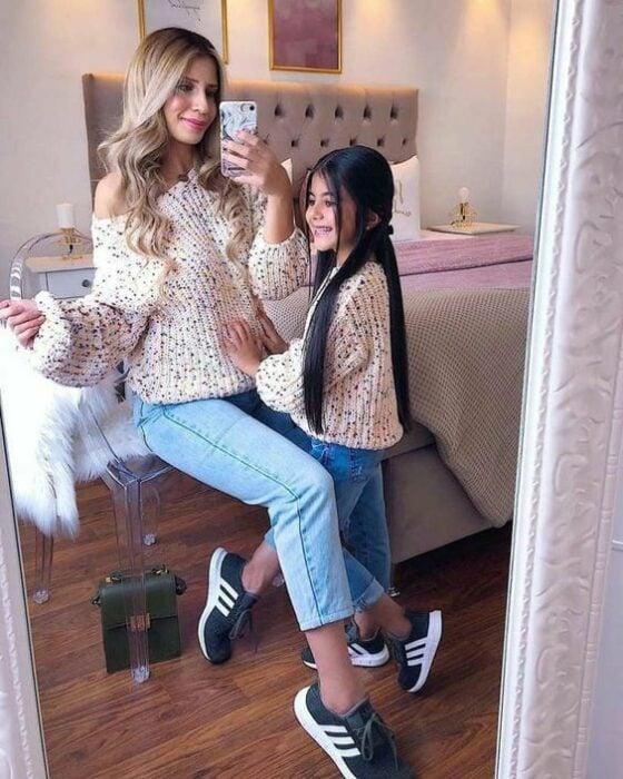 Madre de cabello rubio e hija pequeña de cabello largo y lacio se toman selfie frente al espejo  recargadas en la cama mientras usan jeans claros, tenis negros con rayas blancas y un suéter claro con bolitas negras