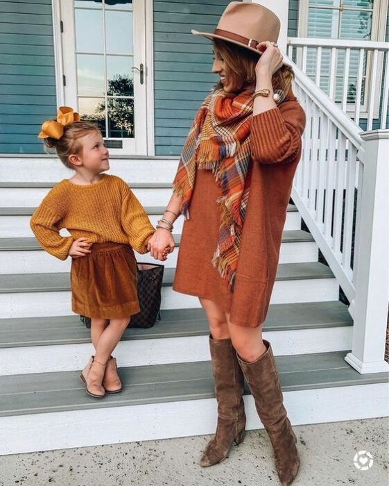 Mother and daughter pose on the steps of a blue house while the girl wears a brown corduroy skirt, yellow sweater, beige ankle boots and a high bun with a large yellow bow and the mother wears a long orange dress with a colored plaid pashmina orange, blue and yellow with brown high boots and a beige hat