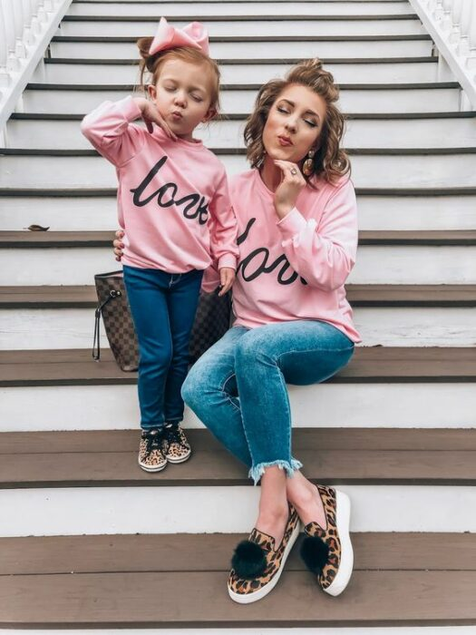 Mother and little daughter do 'duck face' on white steps while both wear dark jeans, 'animal print' tennis shoes, pink sweatshirt that says the word love in cursive letters and the girl has a high bun with a big pink bow and the mother short curly hair with a little bun on top