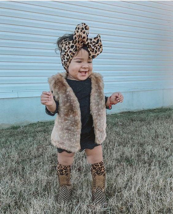 Bebé con moño grande de animal print en la cabeza vistiendo blusita negra, botitas cafés y chaleco de peluche color beige