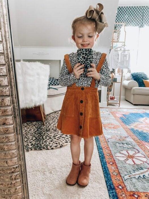 Niña pequeña rubia tomándose selfie frente al espejo con moño grande café en la cabeza y vistiendo blusa de animal print de leopardo con faldita naranja de pana