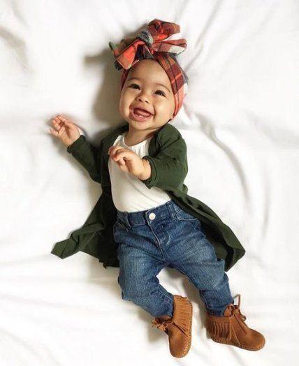 Bebé sonriente acostada en la cama con banda de colores en la cabeza, blusita blanca, cardigan verde esmeralda y pantalón de mezclilla