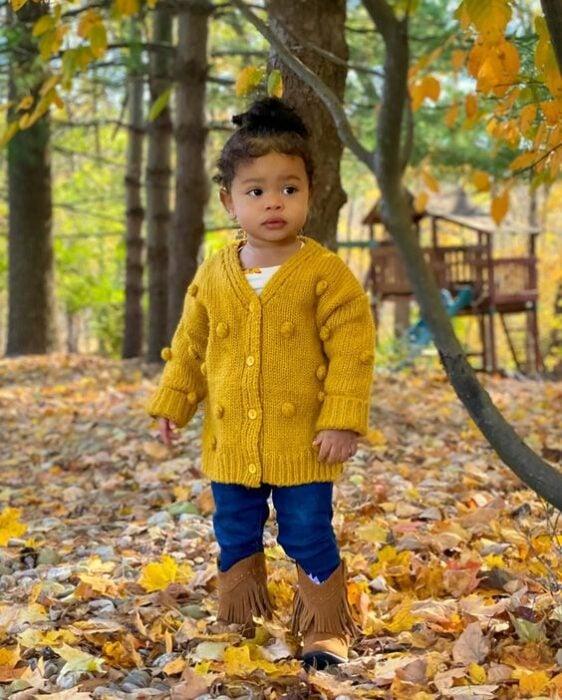 Niña pequeña de cabello rizado peinado en un chongo alto vistiendo suéter amarillo, jeans oscuros y botitas cafés