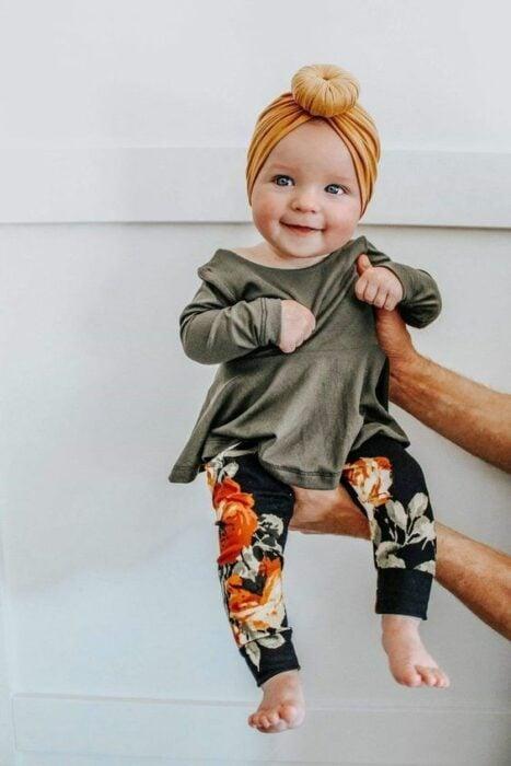 Bebé cargada en brazos con vestidito verde y leggins negros con flores naranjas