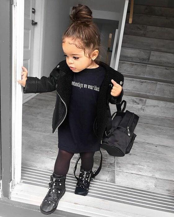 Niña pequeña con chonguito alto y blusa, chamarra, mallas y botas de color negro con mochilita negra
